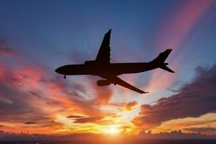 The silhouette of a passenger plane. Flying in sunset Royalty Free Stock Image
