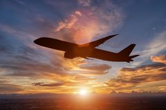 The silhouette of a passenger plane. Flying in sunset Stock Image