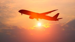 The silhouette of a passenger plane. Flying in sunset Stock Images