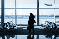 Silhouette of passenger waiting for the flight in airport Stock Photos