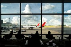 Silhouette of passenger waiting flight for travel in lounge at a. Irport terminal. Interior airport Royalty Free Stock Photography