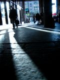 Silhouette people. Man walking down the street, backlit by the afternoon sun stock images
