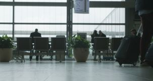 Silhouette of People in airport terminal walking with luggage. People walking through an airport terminal with luggage stock footage