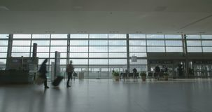 Silhouette of People in airport terminal walking with luggage. People walking through an airport terminal with luggage stock video