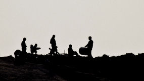 Silhouette of people on the beach. Silhouette of a group of people playing on rocks on the beach Stock Image