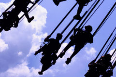 Silhouette of People on Carnival Swings royalty free stock photo