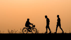 Silhouette of people cycling and walking relax Royalty Free Stock Images