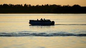 Silhouette of people enjoying boating on a calm lake in Bemidji, Minnesota stock video