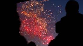 Silhouette people enjoying holiday firework closeup on weekend in night sky 4K. Silhouette people enjoy holiday firework closeup on weekend in night sky 4K. Fans stock video footage