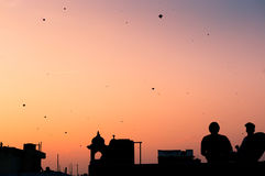 Silhouette of people flying kites Stock Images