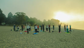 Silhouette of people group practicing yoga on beach at sunrise royalty free stock photos