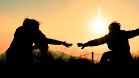 Silhouette of people helping each other hand by hand royalty free stock images