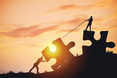 Silhouette people helping to connect jigsaw and puzzle to success royalty free stock images
