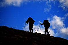 Silhouette of People Hiking on Mountainside Stock Photo