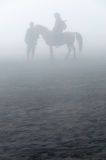 Silhouette of people and horses in fog or mist Royalty Free Stock Image
