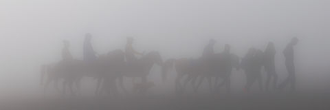 Silhouette of people and horses in fog or mist Stock Photo