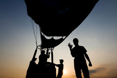 Silhouette of people with hot air balloon in the background at sunset Stock Photos
