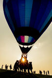 Silhouette of people with hot air balloon with colored envelope at sunset Royalty Free Stock Image