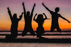 Silhouette of People Jumping Stock Photo