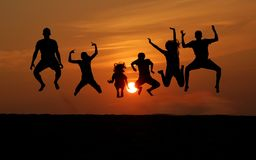 Silhouette of People Jumping at Sunset. A silhouette of people jumping at sunset on the beach Royalty Free Stock Image
