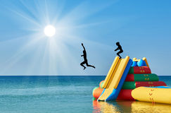 Silhouette of people jumping from the water slide stock images