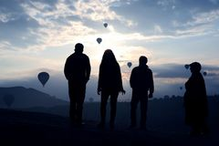 Silhouette of people looking at morning flight of passenger balloons in Cappadocia. The Silhouette of people looking at morning flight of passenger balloons in stock photography