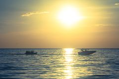 Silhouette of people playing banana boat on the sea with beautiful view of sunset light in the background at Chao Lao Beach. Silhouette of people playing banana Royalty Free Stock Images