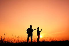 Silhouette people playing musical. In the sunset stock photography