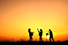 Silhouette people playing musical. In the sunset stock photo