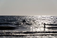 Silhouette of People playing, swimming in the waves in the island of Patmos, Greece in summer time stock image