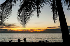 Silhouette people relax on the beach with color of sunset Stock Photography