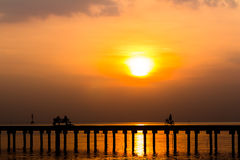 Silhouette people ride bicycle and sitting on the bridge Royalty Free Stock Image