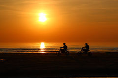 Silhouette of people are riding a motorcycle at the sunset   Royalty Free Stock Images