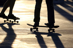 Silhouette of people riding on a skateboard in the sun. The silhouette of people riding on a skateboard in the sun Royalty Free Stock Image