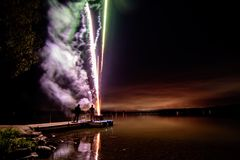Fireworks over lake in beautiful landscape Royalty Free Stock Images
