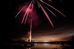 Fireworks over lake in beautiful landscape Stock Photos