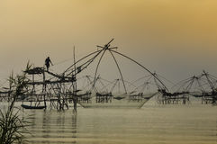 Silhouette people standing on fishing equipment,Patthalung,Thail. Silhouette people standing on fishing equipment background at sunrise time Stock Photography
