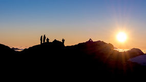 Silhouette of people standing on a mountain ridge Stock Image
