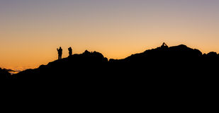 Silhouette of people standing on a mountain ridge Royalty Free Stock Photo