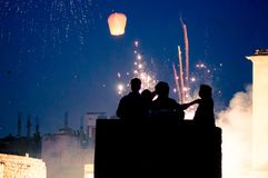 Silhouette of people standing in front of fireworks and sky lant. Silhouette of people standing on a roof with fireworks and sky lanterns in the background. Shot Royalty Free Stock Photography