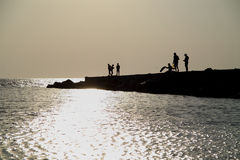 Silhouette people on sunset. Sea Royalty Free Stock Photography