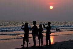 Silhouette of people taking sunset picture on beach Royalty Free Stock Photo