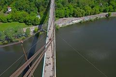 Silhouette of people traveling across bridge Royalty Free Stock Photo