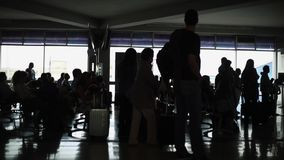 Silhouette of people waiting at Airport Terminal. Silhouettes of unrecognizable group of people standing around an airport terminal.  Shades of black and white stock video