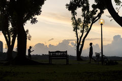 Silhouette of people walk and jog at during evening sunset. Warm tones. Royalty Free Stock Photos