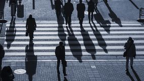 Silhouette people walk on pedestrian crosswalk at the junction royalty free stock photography
