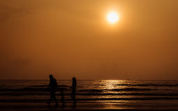 Silhouette people walking on the beach Stock Image