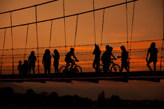 Silhouette people walking on rope bridge Stock Photography