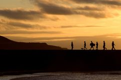 Silhouette of people walking at sunset Stock Photo