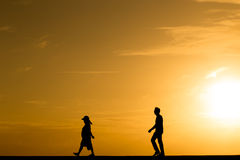 Silhouette people walking at sunset. With orange color filtered Royalty Free Stock Photo